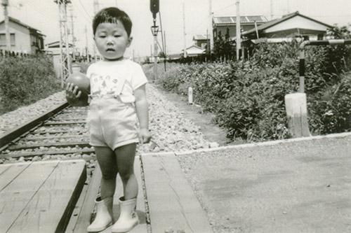 2歳頃の尚さん。電車が大好きで線路で遊ぶ