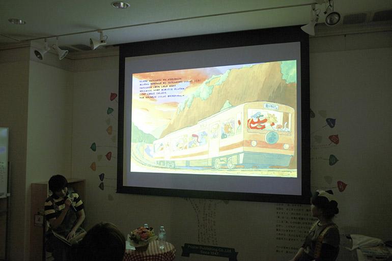 トークショーでは、プロジェクターを利用して投影された大きな絵本を用いて、ナカオさんが『ようかいでんしゃ』の読み聞かせを行ってくださいました